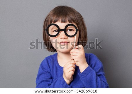 fun kid glasses concept - happy preschool child holding fake black round eyeglasses for playing like adult or dressing up as smart nerd,studio shot - stock photo