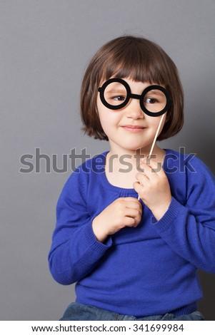 fun kid glasses concept - smiling preschool child holding fake black round eyeglasses for playing like adult or dressing up as smart nerd,studio shot - stock photo