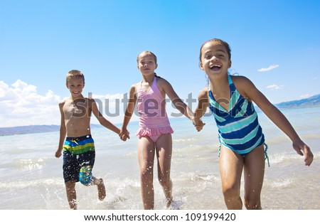 Fun Kids playing at the Beach - stock photo