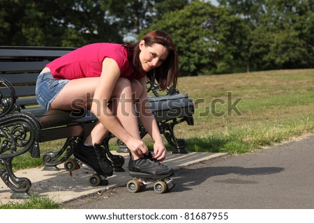 Fun leisure activity for beautiful young long legged girl putting on her roller skates sitting on park bench in summer sunshine. She is wearing a red top and denim cut off shorts. - stock photo