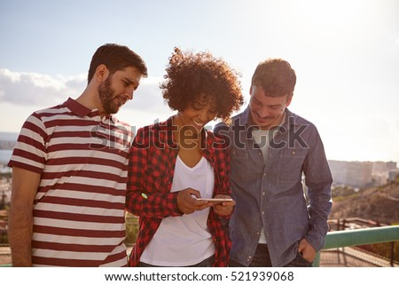 Fun loving friends sharing a memory while looking at the cell phone the girl with a toothy smile holds