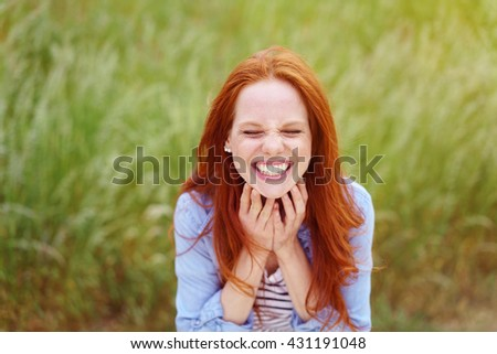 Fun loving pretty young redhead woman with a goofy expression grinning at the camera while posing in a field of long grass - stock photo
