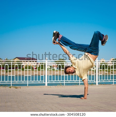 Fun man dancing. Has yellow t-shirt, blue jeans, gray shoes sneakers, slim sport body. Motion on great urban city. Amazing portrait. Sports acrobatic handstand. Fitness concept. Jump creative unique - stock photo