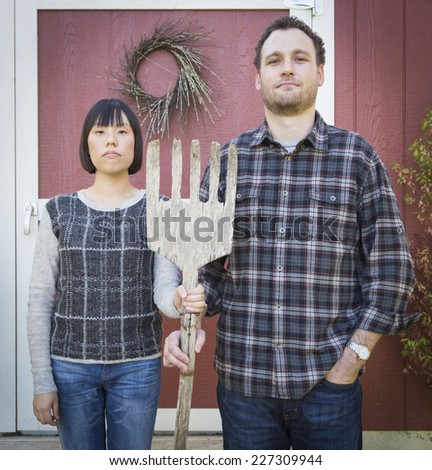 Fun Mixed Race Couple Portrait Simulating the American Gothic Painting by Grant Wood. - stock photo