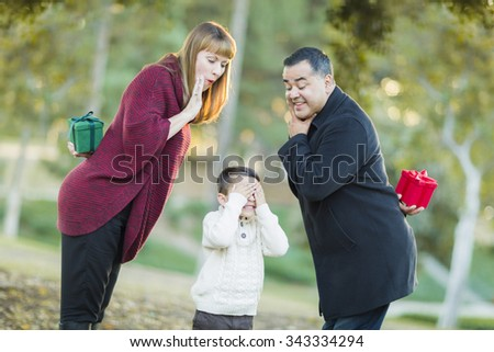Fun Mixed Race Parents With Gifts for Young Boy Hiding His Eyes. - stock photo
