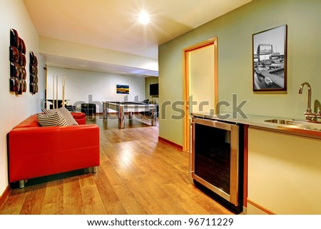 Fun play room home interior. Basement room without windows with pool table, TV, games. - stock photo
