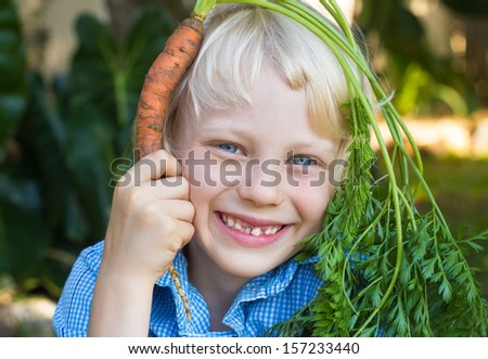 Fun portrait of a cute child holding a homegrown organic carrot over his head outdoors. - stock photo