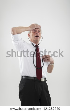 Fun portrait of a hypochondriac man worried by his health with one hand to his forehead while listening to his heart using a stethoscope with the other, or as a warning of heart disease in the elderly - stock photo