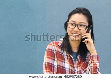 Fun portrait of a laughing attractive young Asian woman wearing glasses chatting on a mobile phone laughing at the camera, upper body over blue with copy space - stock photo
