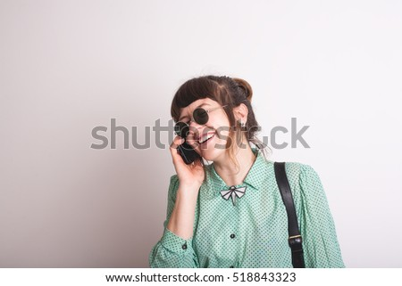 Fun portrait of a laughing attractive young woman wearing glasses talking on the mobile phone and laughing