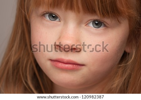 Fun Portrait of an Adorable Red Haired Girl on a Grey Background.