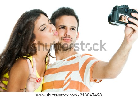 Fun portrait of cute couple taking self portrait with camera.Isolated on white background. - stock photo
