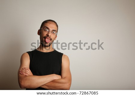 Fun portrait of man sticking tongue out with arms crossed, wearing a-shirt anainst seamless wall background. Copyspace.