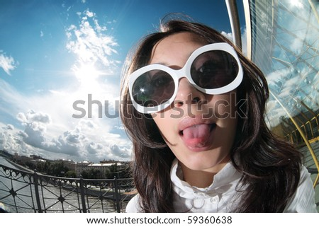 Fun portrait of young woman in funky sunglasses sticking her tongue out