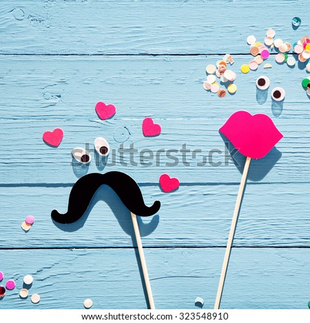 Fun romantic couple from photo booth accessories with a mustache with eyes surrounded by hearts eyeing a lady with luscious red lips and confetti flowers in her hair, on a rustic blue wood background - stock photo