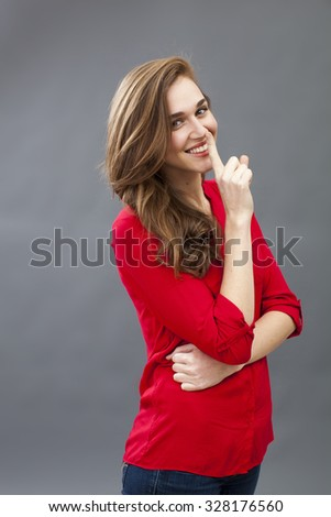 fun secret concept - beautiful 20s woman wearing red shirt smiling in showing a finger on her lips for discretion,profile view,studio shot - stock photo