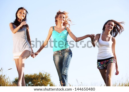fun smile girlfriends run by green field sun is shine - stock photo