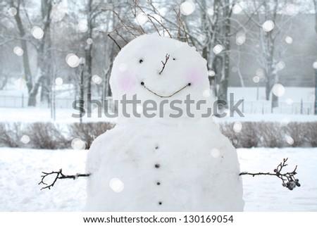 Fun snowman in park. - stock photo