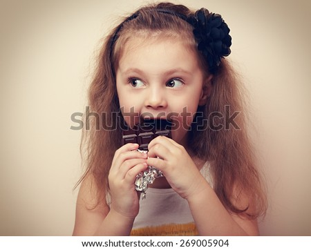 Fun surprising kid girl eating dark chocolate. Vintage closeup portrait - stock photo