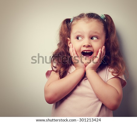 Fun surprising kid girl with open mouth looking on empty copy space. Vintage closeup portrait - stock photo