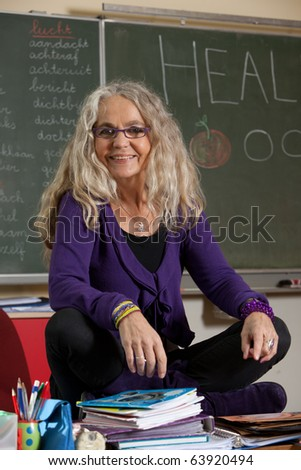 Fun teacher sitting on top of her desk in the classroom - stock photo