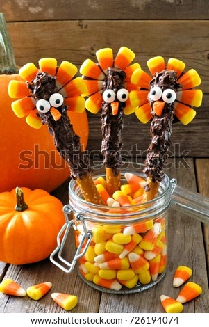 Fun Thanksgiving turkey pretzel sticks with candy corn, still life against a wood background