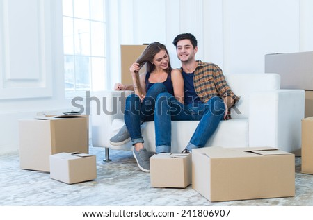 Fun while moving new flat. Young and beautiful couple is moving to new apartment surrounded with plenty of cardboard boxes. Both are smiling