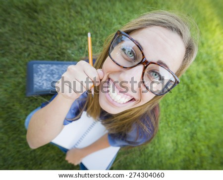 Fun Wide Angle Portrait of Pretty Young Woman with Books and Pencil Sitting in the Grass Outdoors. - stock photo
