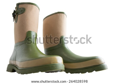 Fun wide low angle view of a pair of rugged green and beige calf-high gardening boots with heavy soles isolated on white - stock photo