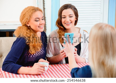Fun with best friends. Three young beautiful female friends sitting in cafe and showing photos on smartphone - stock photo