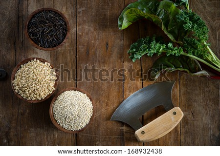 Fun with food, small wood bowls filled with brown rice, quinoa and wild rice on the left.  Kale, Swiss chard and an ulu knife on the right. Copy space dead center. This is shot on a wood table. - stock photo