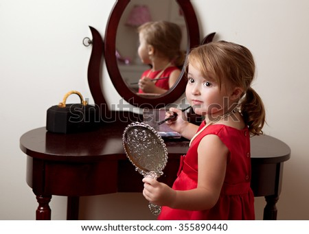 Fun with Makeup.  Adorable preschooler at her bedroom vanity playing with makeup.  Room for your text. - stock photo