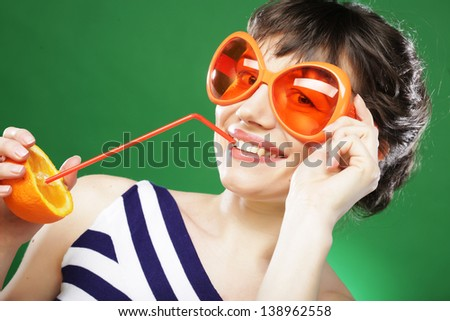 fun woman with oranges over green background - stock photo