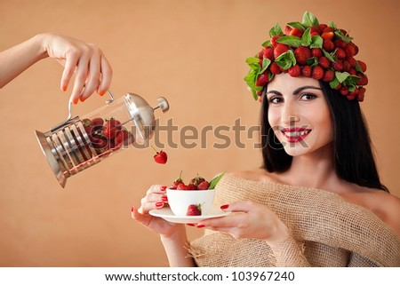 Fun woman with strawberry hat  and cup of strawberry tea and hand with tea-pot full with strawbwrrys - stock photo