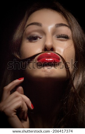 Fun Young Woman Using her hair as a Mustache - stock photo