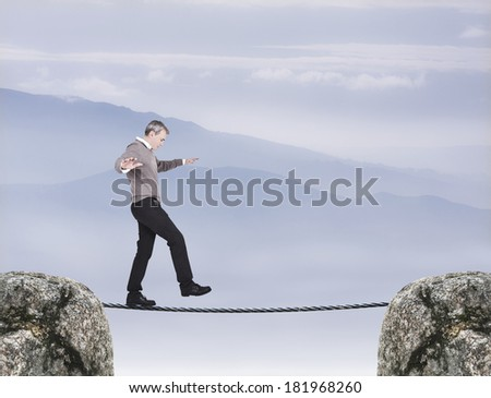 funanbulista clown balancing on a tightrope in the air - stock photo