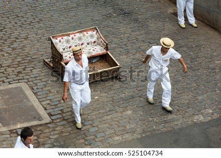 FUNCHAL, MADEIRA, PORTUGAL - SEPTEMBER 2, 2016: Toboggan riders moving traditional cane sledge downhill on the streets of Funchal. Monte park, Madeira island, Portugal