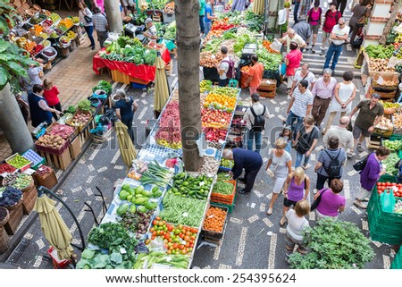 FUNCHAL, PORTUGAL - AUG 01: Tourists visiting the vegetable market of the famous Mercado dos Lavradores on August 01, 2014 at Funchal, capital city of Madeira, Portugal - stock photo