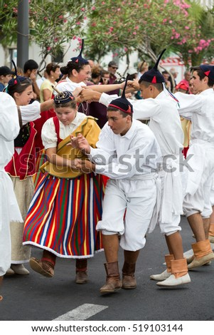 FUNCHAL, PORTUGAL - SEPTEMBER 4, 2016: Dancers with local costumes perform a folk dance during the parade of Wine Festival in Funchal on the Madeira, Portugal.