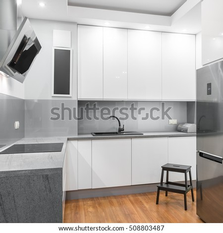 Functional white kitchen with wooden step stool, silver fridge and exhaust hood