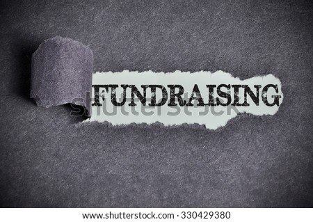 fundraising word under torn black sugar paper. - stock photo