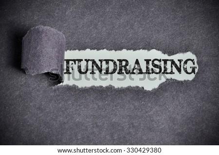 fundraising word under torn black sugar paper. - stock photo