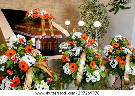 Funeral hall with wooden coffin and flower decoration, prepared for burial ceremony - stock photo