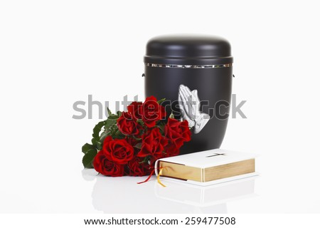 Funeral, urn with praying hands, white bible and red roses - stock photo