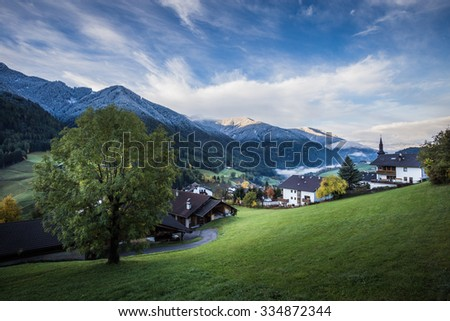 Funes Valley, Dolomites, Italy. Autumnal view of the valley, with some snow, with colorful trees and some houses during early morning. St. Peter village.