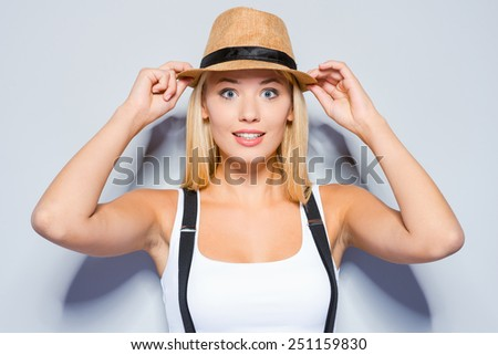 Funky beauty. Beautiful young blond hair women making a face and adjusting her hat while standing against grey background   - stock photo