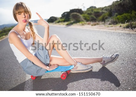 Funky blonde sitting on her skateboard on a deserted road making rock and roll hand gesture - stock photo