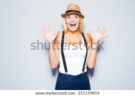 Funky emotions. Beautiful young blond hair women making a face while standing against grey background   - stock photo