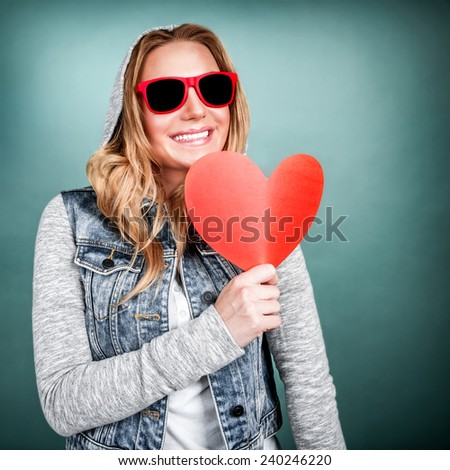 Funky girl in love, isolated on blue background, holding in hands red paper heart, romantic gift on Valentine day, adolescence affection concept - stock photo