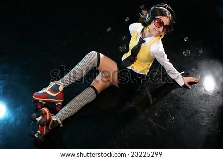 Funky girl with rollerskates and headphones isolated on black disco dancefloor, enjoy - stock photo